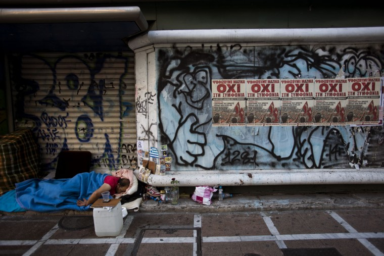 "A homeless sleeps at the entrance of a closed store with posters reading ''No'' in central Athens, Monday, July 6, 2015. Greece's Finance Minister Yanis Varoufakis has resigned following Sunday's referendum in which the majority of voters said ""no"" to more austerity measures in exchange for another financial bailout. (AP Photo/Emilio Morenatti)"