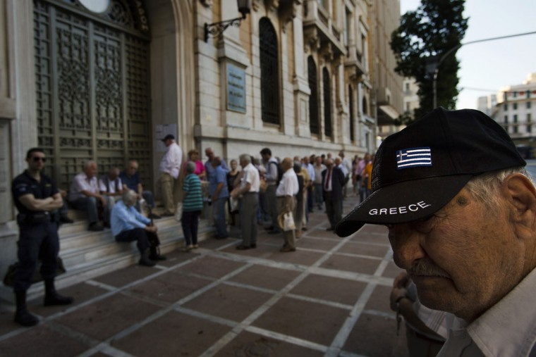Pensioners wait outside the main gate of the national bank of Greece to withdraw a maximum of 120 euros ($134) in central Athens, Thursday, July 9, 2015. With a deadline just hours away to come up with a detailed economic reform plan, Greece requested a new three-year rescue from its European partners Wednesday as signs grew its economy was sliding toward free-fall without an urgently needed bailout. (AP Photo/Emilio Morenatti)
