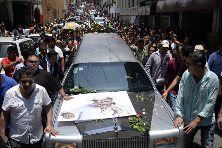 "A hearse transporting the coffin containing the remains of Mexican ballad singer Joan Sebastian leads his funeral procession through the streets of Cuernavaca, Mexico, Wednesday, July 15, 2015. The Grammy and Latin Grammy award winner died Monday. He was best known for sentimental love songs such as, ""Tatuajes"" and ""Secreto de Amor."" He was 64. (AP Photo/Tony Rivera)"