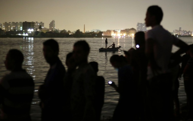 Egyptian volunteers look for victims of a passenger boat after it sank in the river Nile in Giza, south of Cairo, Egypt, Thursday, July 23, 2015. Egypt's Interior ministry says more than a dozen civilians have drowned when the passenger boat traveling down the Nile near Cairo collided with a scow, causing the boat to capsize. (AP Photo/Amr Nabil)