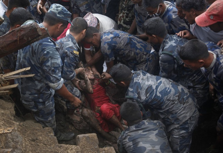 Nepalese army and police rescues team recover a dead body of a victim from the debris after a landslide in Lumle village, about 200 kilometers (125 miles) west of Kathmandu, Nepal, Thursday, July 30, 2015. Landslides in a mountain area of Nepal buried three villages Thursday, killing several people, authorities said.(AP Photo/Niranjan Shrestha)