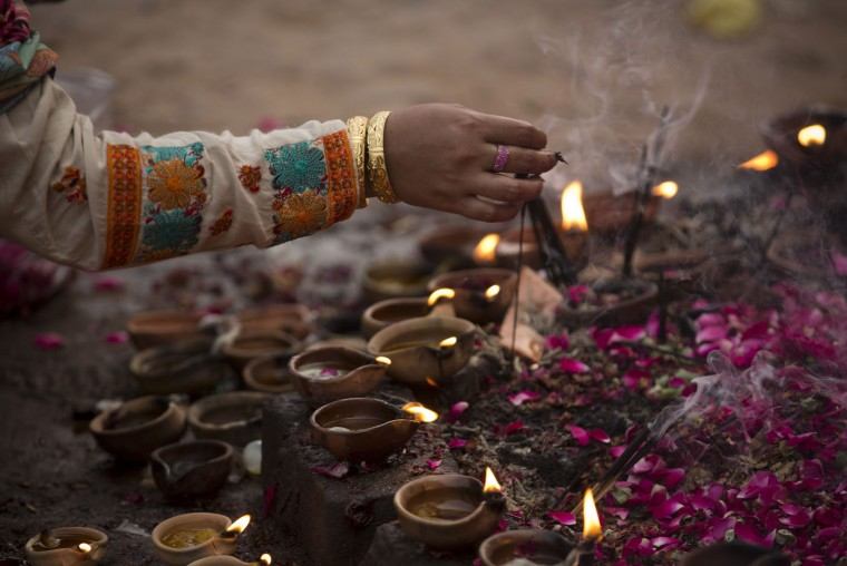 A Pakistani Muslim devotee lights oil clay lamps at a local shrine in suburbs of Islamabad, Pakistan, Thursday, July 23, 2015. People usually visit shrines on Thursday and Friday to get their wishes fulfilled. (AP Photo/B.K. Bangash)