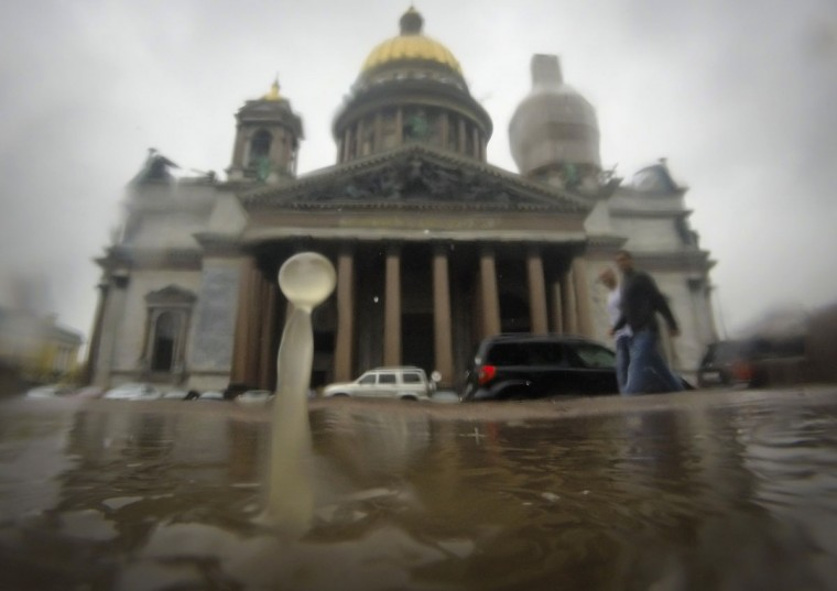Raindrops fall into a puddle in St.Petersburg, Russia, Tuesday, July 7, 2015, with the city's landmark St. Isaac's Cathedral in the background. Cyclone from the west brought rains to St. Petersburg on Tuesday. (AP Photo/Dmitry Lovetsky)