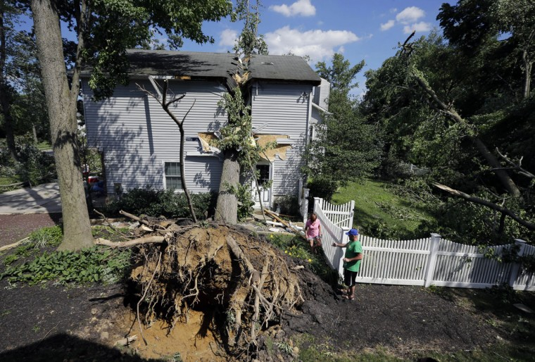 Joe Higgins, right, helps Debbie Epifano walk past a large tree that crashed through their home during a storm Tuesday night in Gibbstown, N.J., Wednesday, June 24, 2015. The home suffered major structural damage, but no one was injured. Gloucester, Camden, Burlington and Salem counties saw the most damage from the ferocious storms that barreled through the region Tuesday night. (AP Photo/Mel Evans)