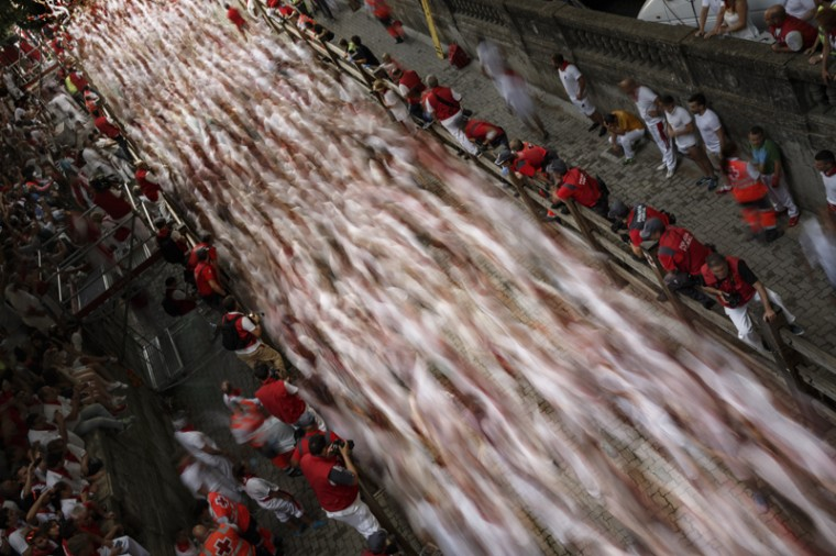 In this slow-shutter-speed picture, revelers run with a Jandilla's ranch fighting bull during the running of the bulls of the San Fermin festival in Pamplona, Spain, on Tuesday. Revelers from around the world turned out here to kick off the festival with a messy party in the Pamplona town square, one day before the first of eight days of the running of the bulls. (Daniel Ochoa de Olza/AP)