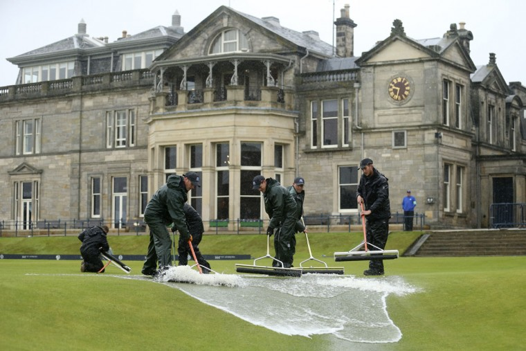Groundskeepers use rollers to clear excess water from the first tee after play was delayed by rain during the second round of the British Open Golf Championship at the Old Course, St. Andrews, Scotland, Friday, July 17, 2015. (AP Photo/Peter Morrison)