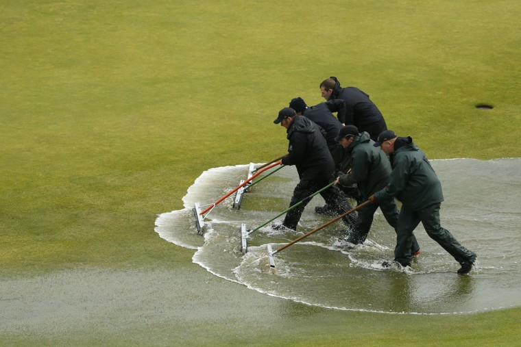 Groundskeepers clear rain water from the tenth green after rain delayed play during the second round of the British Open Golf Championship at the Old Course, St. Andrews, Scotland, Friday, July 17, 2015. (AP Photo/Jon Super)