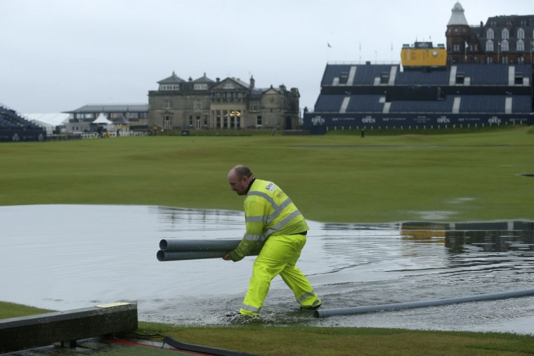 A worker lays down pipes to clear excess water on the course as rain delays play during the second round of the British Open Golf Championship at the Old Course, St. Andrews, Scotland, Friday, July 17, 2015. (AP Photo/Peter Morrison)
