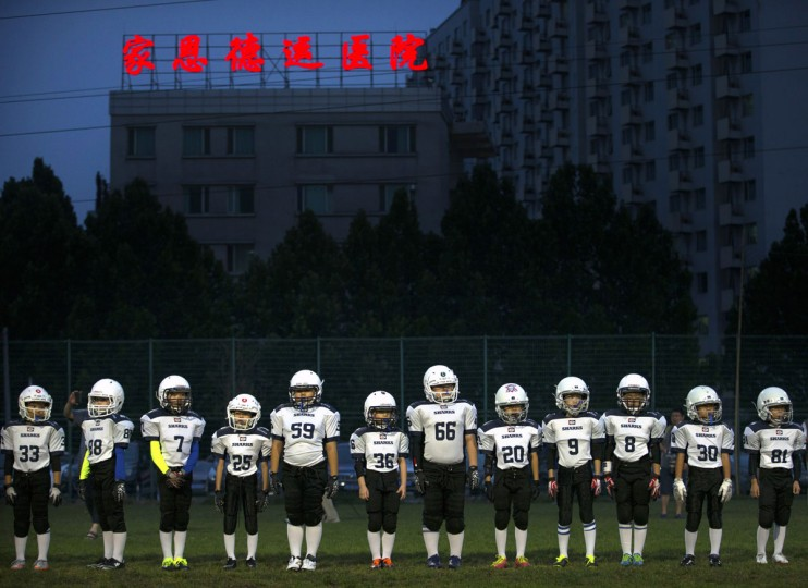 Members of the Sharks team line up before the start of their American football game in Beijing. Chinaís capital might seem like an unlikely place to find American football, but interest among Chinese youth is growing. (AP Photo/Mark Schiefelbein)