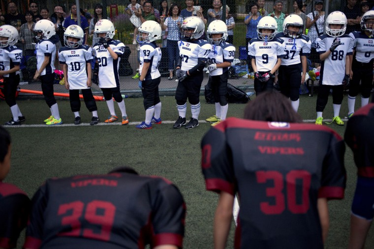 Members of the Vipers team, in foreground, bow to members of the Sharks team after their American football game in Beijing. Chinaís capital might seem like an unlikely place to find American football, but interest among Chinese youth is growing. (AP Photo/Mark Schiefelbein)