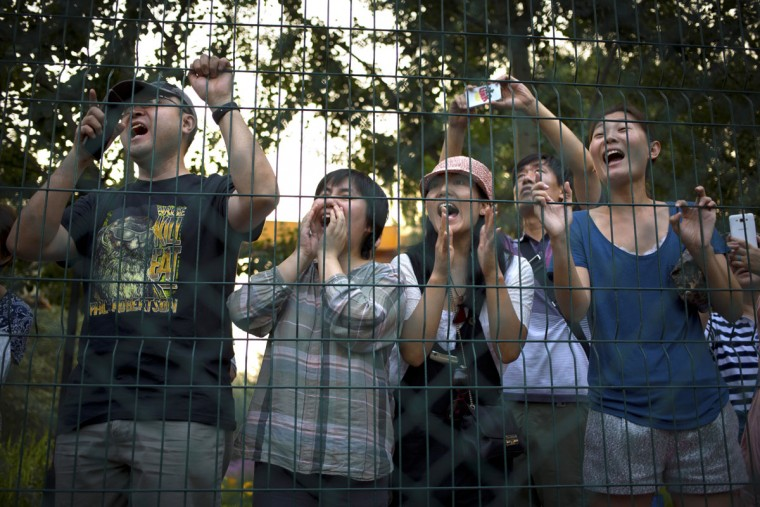 Parents and spectators cheer during an American football game in Beijing. Chinaís capital might seem like an unlikely place to find American football, but interest among Chinese youth is growing. (AP Photo/Mark Schiefelbein)