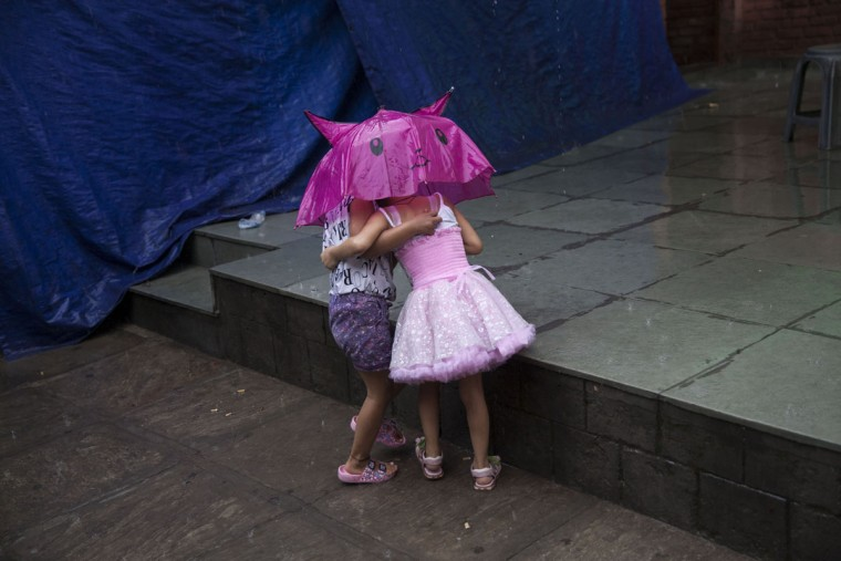 Exile Tibetan kids play in the rain at a Tibetan colony in New Delhi, India, Tuesday, July 7, 2015. (AP Photo/Tsering Topgyal)