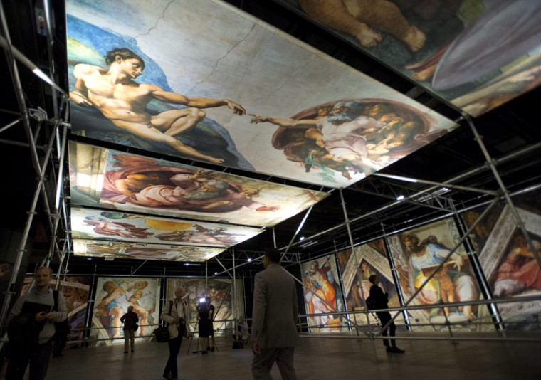 Members of the media preview the photo reproductions at the world premiere of Michelangelo's Sistine Chapel on Tuesday, in Montreal. The exhibit is scheduled until Oct. 12. (Ryan Remiorz/The Canadian Press via AP)