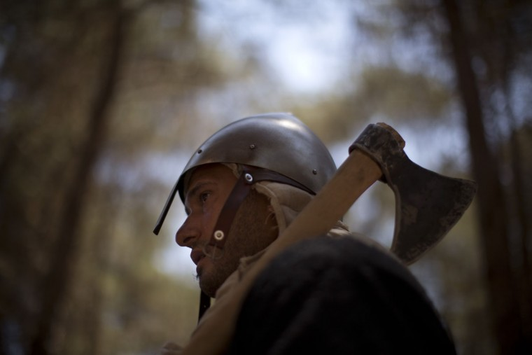 In this Saturday, July 4, 2015 photo, an Israeli member of a knight club gets ready for the reenactment of the Battle of Hattin in Lavi Forest, northern Israel. Replete with swords, shields and body armor, some 60 history buffs marched 27 kilometers (17 miles) this weekend while re-enacting the Battle of Hattin, one of the most significant battles of the Middle Ages. (AP Photo/Oded Balilty)