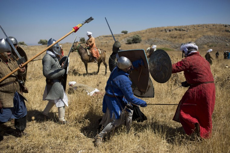 In this Saturday, July 4, 2015 photo, Israeli and Russian members of knight clubs participate in the reenactment of the Battle of Hattin in Horns of Hattin, northern Israel. Replete with swords, shields and body armor, some 60 history buffs marched 27 kilometers (17 miles) this weekend while re-enacting the Battle of Hattin, one of the most significant battles of the Middle Ages. (AP Photo/Oded Balilty)