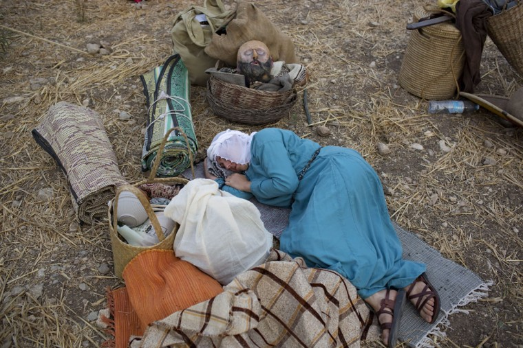 In this Thursday, July 2, 2015 photo, an Israeli member of a knight club rests in the camp before marching 27 kilometers (17 miles) to the reenactment of the Battle of Hattin from the ancient northern city of Zippori to Horns of Hattin, northern Israel. Some 60 history buffs are re-enacting the famed battle near an extinct volcano in northern Israel overlooking the Sea of Galilee, where Saladin's army defeated the crusaders at the end of the 12th century. (AP Photo/Oded Balilty)