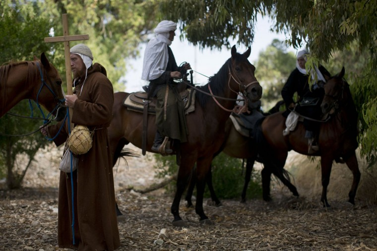 In this Friday, July 3, 2015 photo, Israeli and Russian members of knight clubs get on their horses before marching 27 kilometers (17 miles) to the reenactment of the Battle of Hattin from the ancient northern city of Zippori to Horns of Hattin, northern Israel. About a third of the participants arrived with their elaborate gear from Russia. The project is supported by the Lower Galilee Regional Council. (AP Photo/Oded Balilty)