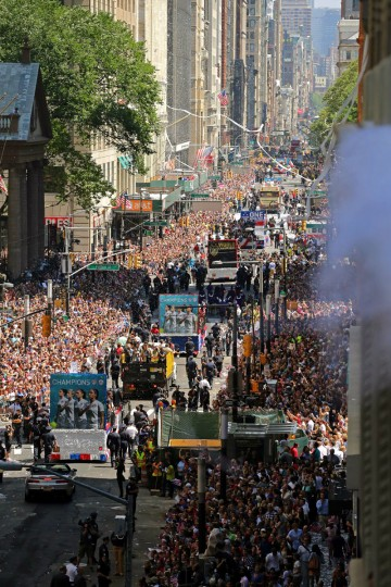 The U.S. Women's World Cup team stands on floats as they move through thousands of fans along Broadway, Friday, July 10, 2015 in New York in a view from 150 Broadway. The U.S. defeated Japan 5-2 on Sunday in Canada to win the World Cup. (AP Photo/Adam Hunger)