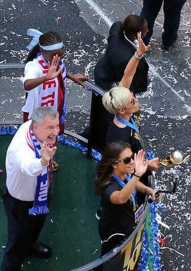 New York City Mayor Bill deBlasio waves along with U.S. women's World Cup championship team members Carli Lloyd, right and Megan Rapinoe, holding the World Cup trophy, on a float during a ticker tape parade in New York, Friday, July 10, 2015.. (AP Photo/Adam Hunger)