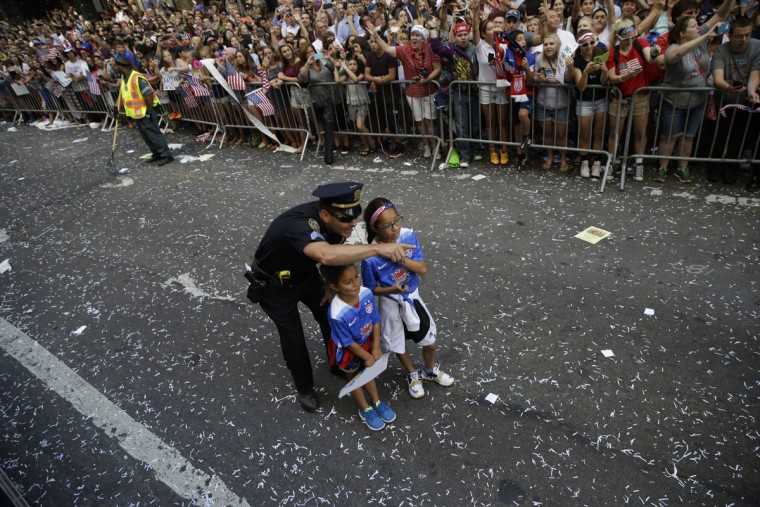 A police officer with two U.S. women's soccer team fans points as the floats with players makes its way up Broadway's Canyon of Heroes during the ticker tape parade to celebrate the World Cup victory, Friday, July 10, 2015, in New York. (AP Photo/Mary Altaffer)