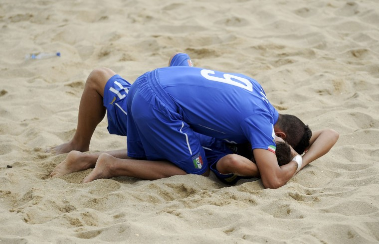 Italy's Zurlo and Palmacci, on the sand, react after their defeat against Tahiti during their FIFA Beach Soccer World Cup semi-final match in Espinho, Portugal, Saturday, July 18, 2015. Tahiti win on penalties 3-1 after a 6-6 draw. (AP Photo/Paulo Duarte)