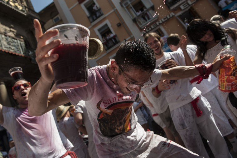 A reveler celebrates during the launch of the 'Chupinazo' rocket, to celebrate the official opening of the 2015 San Fermin Fiestas, in Pamplona, northern Spain, Monday, July 6, 2015. (AP Photo/Alvaro Barrientos)