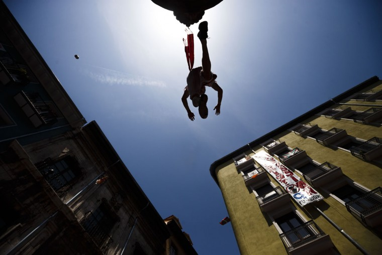 A reveler jumps from high towards his friends as they celebrate during the launch of the 'Chupinazo' rocket, to celebrate the official opening of the 2015 San Fermin fiestas in Pamplona, Spain, Monday, July 6, 2015. (AP Photo/Daniel Ochoa de Olza)