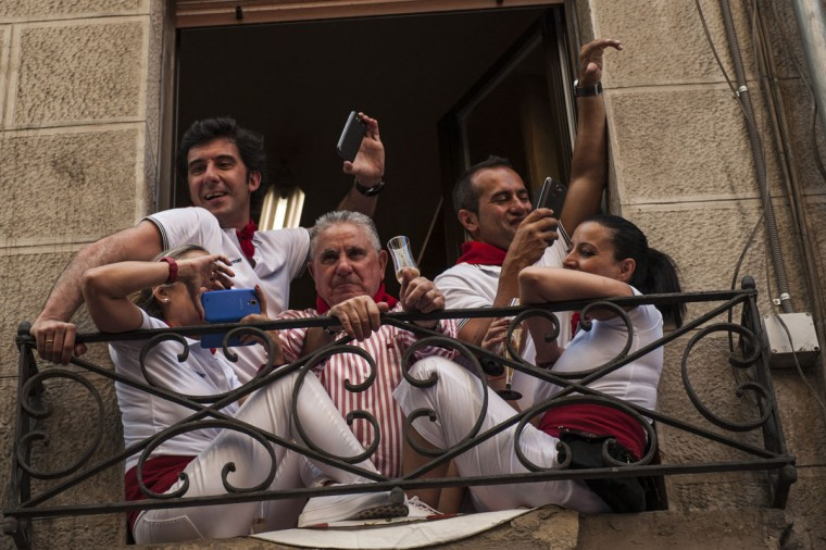 People look on from a balcony while they celebrate during the launch of the 'Chupinazo' rocket, to celebrate the official opening of the 2015 San Fermin Fiestas, in Pamplona, northern Spain, Monday, July 6, 2015. (AP Photo/Alvaro Barrientos)