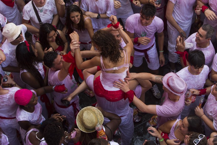 """A girl is held by other revelers during the launch of the """"Chupinazo"""" rocket, to celebrate the official opening of the 2015 San Fermin fiestas in Pamplona, Spain, Monday, July 6, 2015. (AP Photo/Andres Kudacki)"""