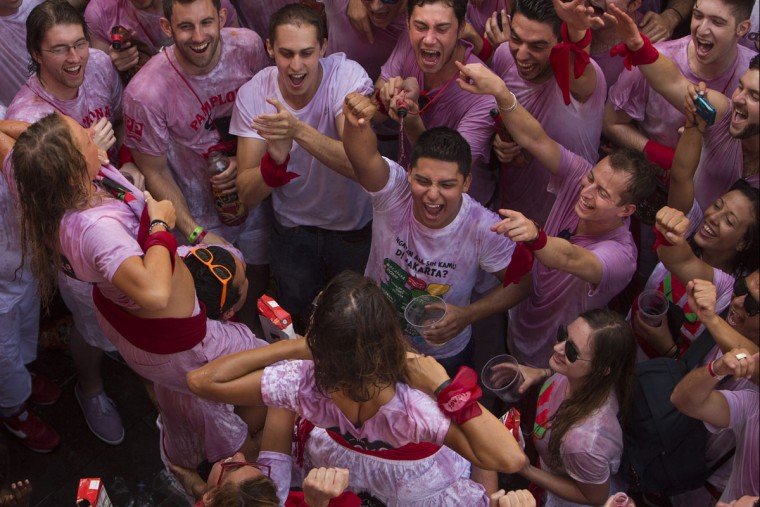 "Revelers shout as girls pull up their t-shirts during the launch of the ""Chupinazo"" rocket, to celebrate the official opening of the 2015 San Fermin festival in Pamplona, Spain, Monday, July 6, 2015. (AP Photo/Andres Kudacki)"
