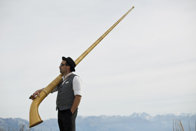 An alpenhorn player carries his instrument near the Lac de Tracouet, situated 2200 meters (7220 feet) above sea level in Haute-Nendaz, canton of Valais, Switzerland, Sunday, July 26, 2015. More than 200 alpenhorn players gathered in Nendaz on Sunday to perform as an ensemble in the Alpenhorn Festival. David Azia/AP