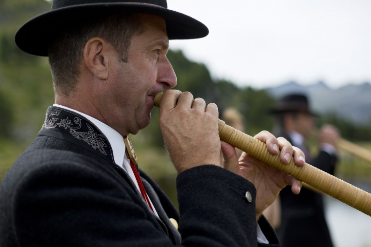 An alpenhorn player from the French Haute Savoie region performs along the Lac de Tracouet, situated 2200 meters (7220 feet) above sea level in Haute-Nendaz, canton of Valais, Switzerland, Sunday, July 26, 2015. More than 200 alpenhorn players gathered in Nendaz on Sunday to perform as an ensemble in the Alpenhorn Festival. David Azia/AP
