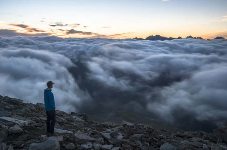 A tourist watches the sunrise above a sea of fog on Eggishorn mountain (2927 meters over sea level), in Fiesch, Switzerland, early Tuesday, July 28, 2015. (Dominic Steinmann/Keystone via AP)