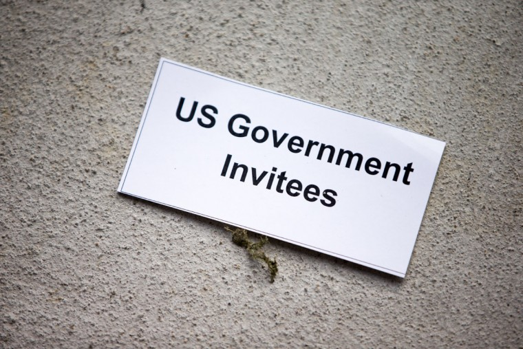 A small card for members of the U.S. Government is placed on the ground outside in front of their new embassy to watch the Cuban flag being raised in Washington, Monday, July 20, 2015. The United States and Cuba restored full diplomatic relations Monday after more than five decades of frosty relations rooted in the Cold War. (AP Photo/Andrew Harnik, Pool)