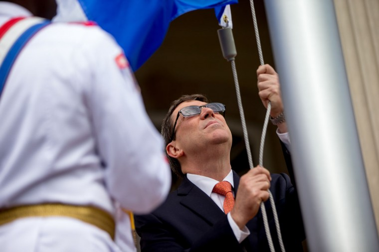Cuban Foreign Minister Bruno Rodriguez, center, raises the Cuban flag over their new embassy in Washington, Monday, July 20, 2015. The United States and Cuba restored full diplomatic relations Monday after more than five decades of frosty relations rooted in the Cold War. (AP Photo/Andrew Harnik, Pool)