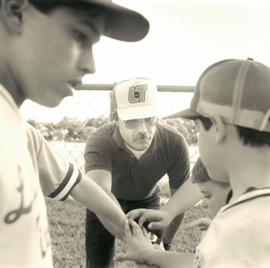 Denny Lessner manager of the Lutherville-Timonium Braves, a Little League team of 11 and 12 year olds, gives his team a pep talk between innings. (Baltimore Sun, 1991)