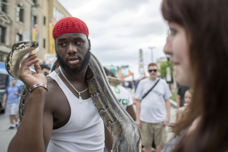 """Aaron Hemsley holds his pet snake, """"Big Momma"""" on Charles Street at Artscape. (Tom Brenner / The Baltimore Sun)"""