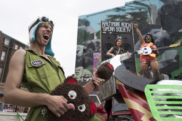 Greg Bowen plays air guitar at the Baltimore Rock Opera Artscape exhibit on North Charles Street. (Tom Brenner / The Baltimore Sun)