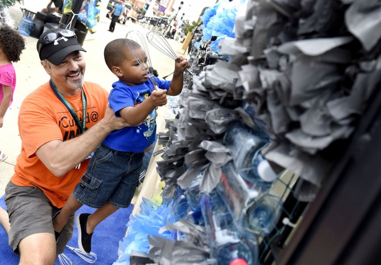 Baltimore, Md. Stephen McAlpine, who works at University of Maryland, Baltimore County, holds up 3-year-old Noah Henderson, of Baltimore, while he drums away on recycled materials at Artscape. (Jon Sham/Baltimore Sun)
