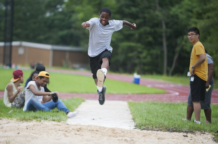 Lynell Shaw, 13, center, jumps into a sand pit while practicing long jumps during a track and field exercise activity at Camp Abilities, hosted by the Maryland School for the Blind.  (Tom Brenner/ Baltimore Sun)