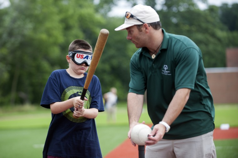 Joey Panasuk, 10, left, is taught by instructor Ben Hutt, right, how to play beep baseball.  Beep baseball is modified by putting speakers into the ball and bases that alert players with sound during game play.  (Tom Brenner/ Baltimore Sun)