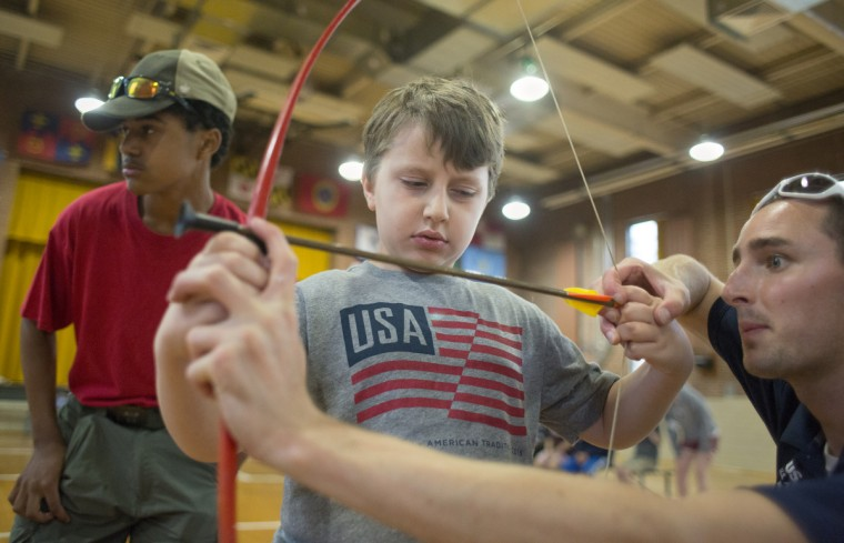 Chris Parrish Jr.,left, of the Clarksville Scouts troop 737 looks downrange as Taylor Runion, 10, center, is taught by camp instructor Matt Mescall, right, how to use a bow and arrow during an archery shooting activity at Camp Abilities, hosted by the Maryland School for the Blind.  (Tom Brenner/ Baltimore Sun)