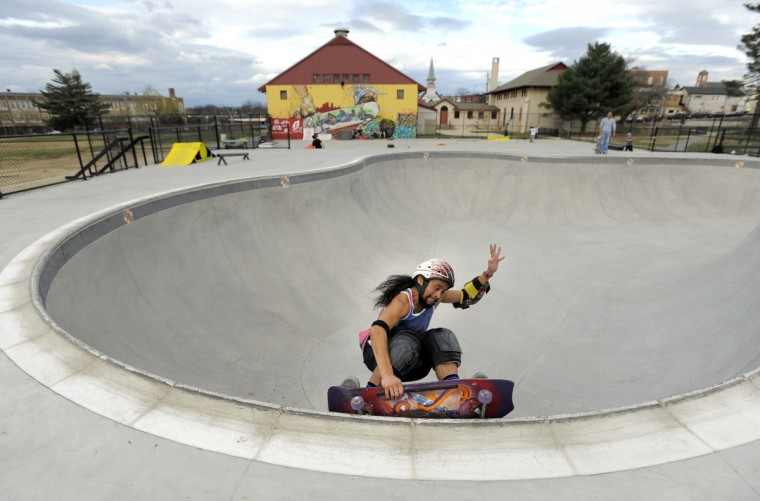 Nino Almazon, 30, a veteran skateboarder from Baltimore grabs his board as he takes a sharp turn while skateboarding in the bowl at the Skatepark of Baltimore in Hampden. (Lloyd Fox/Baltimore Sun)
