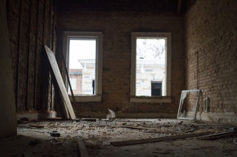 A vacant home in the 900 block of N. Port Street, being deconstructed by city contractors Details - a group who employs people with barriers, including a conviction. (Kalani Gordon, Baltimore Sun)