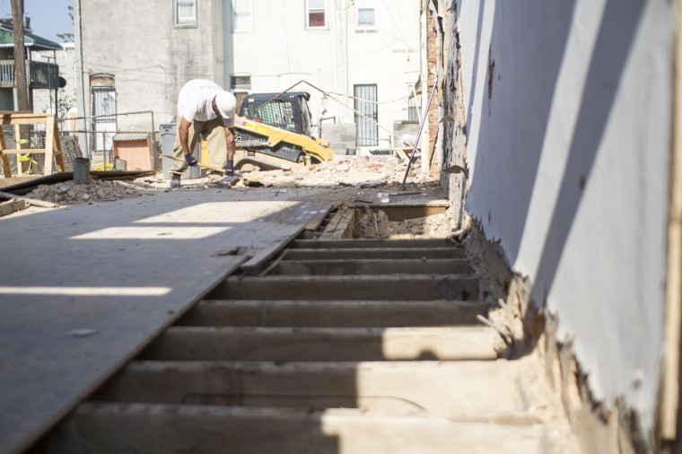 A Details employee pulls up flooring of a home in the south end of the 900 block of Port Street, a block being deconstruction by the group Details. (Kalani Gordon, Baltimore Sun)