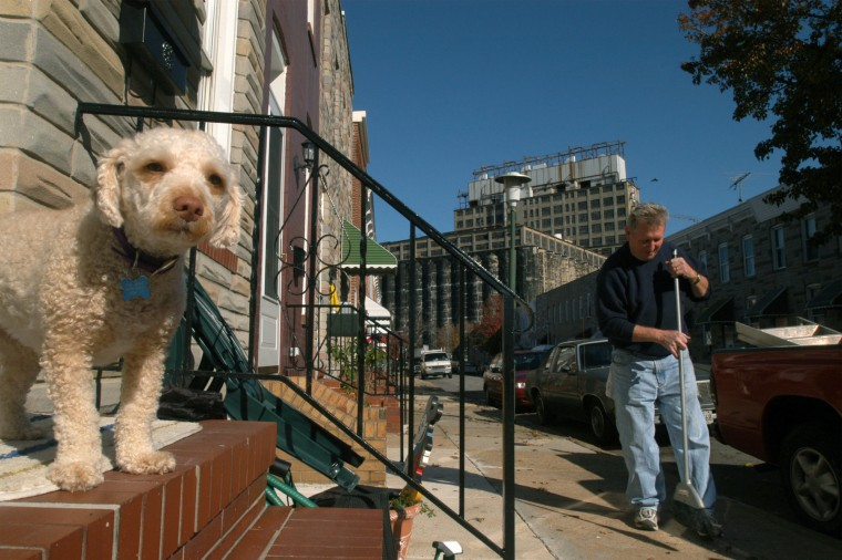 "Nov. 20, 2003: Marvin Bohle sweeps the sidewalk in front of his home on Reynolds St. as his dog, ""Angel"" looks down the street from the porch. Bohle worked 33 years as a grain operator at the grain elevator company behind him, which has been closed about 3 years. (Algerina Pern/Baltimore Sun)"