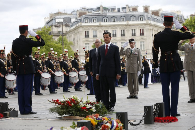 Mexican President Enrique Pena Nieto (center) and French Finance Minister Michel Sapin (rear left) attend a wreath laying ceremony on the tomb of the unknown soldier at the Arc de Triomphe monument in Paris, on Bastille Day, July 14, 2015. (THOMAS SAMSON/AFP/Getty Images)