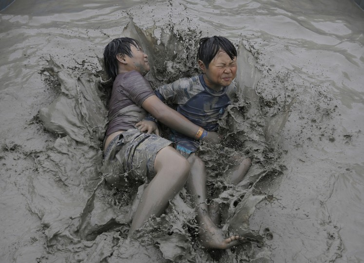 Children wrestle in a mud pool during the Boryeong Mud Festival at Daecheon Beach in Boryeong, South Korea, Saturday, July 18, 2015. The 18th annual mud festival features mud wrestling and mud sliding. (Ahn Young-joon/Associated Press)
