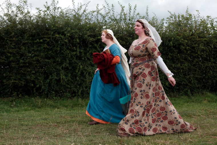 Women wear Medieval garb during the reenactment of the Battle of Agincourt, in Agincourt, northern France, Saturday, July 25, 2015. The French are hosting a reenactment of the clash with England this weekend. More than 800 people in Medieval garb are gathering at the site to commemorate the battle, which was a turning point in the Hundred Years' War. (Associated Press/Thibault Camus)