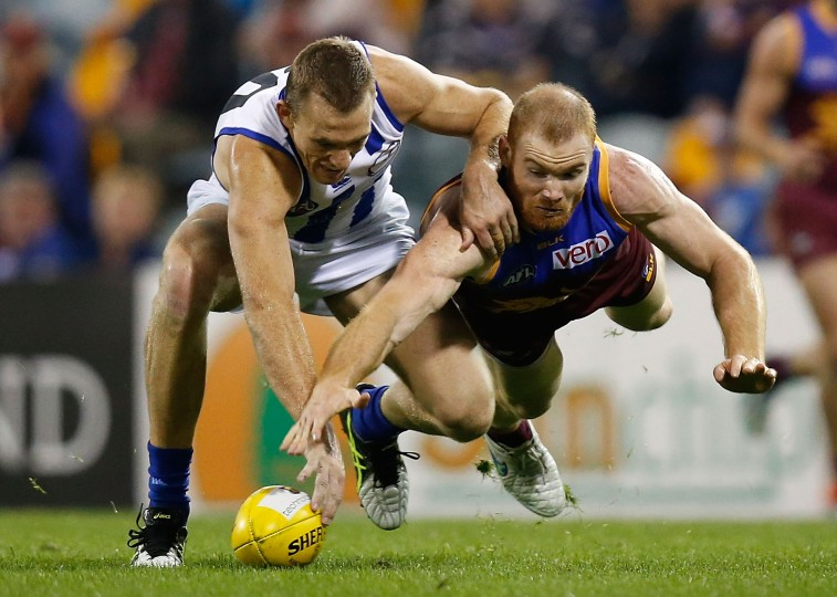 Drew Petrie of the Kangaroos and Daniel Merrett of the Lions in action during the 2015 AFL round 17 match between the Brisbane Lions and the North Melbourne Kangaroos at The Gabba, Brisbane, Australia on July 25, 2015. (Michael Willson/AFL Media/Getty Images)